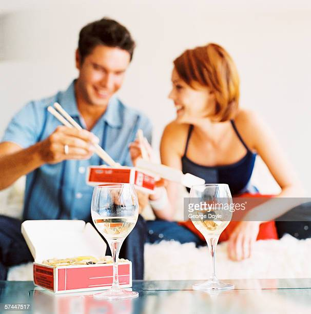 portrait of a couple eating Chinese take-out with white wine