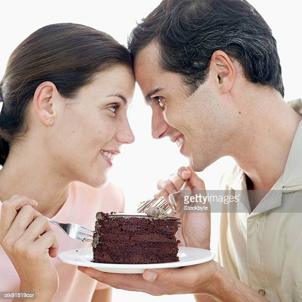 portrait of a couple gazing at each other over a slice of chocolate cake