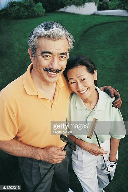 Portrait of a Couple Holding Golf Clubs Standing on a Golf Course