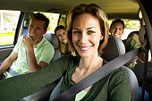 Portrait of a couple in a car with their teenage son and daughter (17-20)