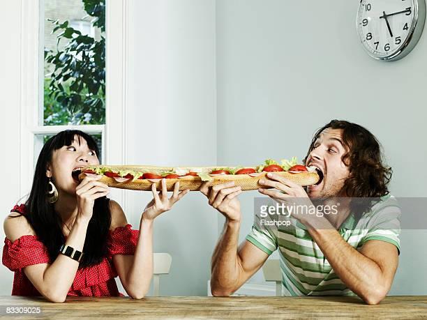 Portrait of a couple sharing a baguette