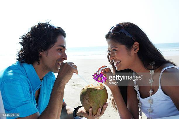 Portrait of a couple sipping on a Coconut drink