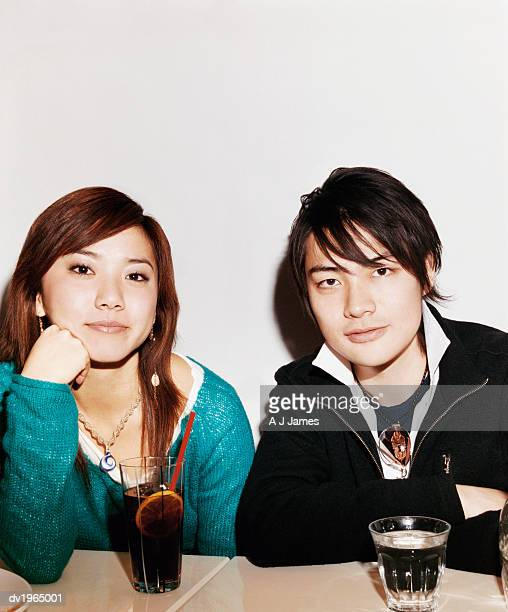 Portrait of a Couple Sitting at a Table With Drinks