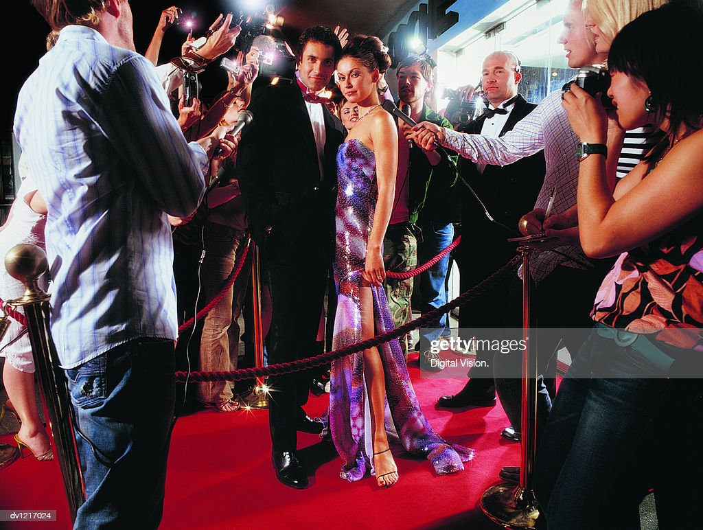Portrait of a Couple Standing on a Red Carpet Being Photographed by Paparazzi at Night : Stock Photo