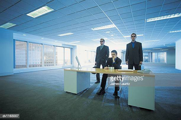 Portrait of a Criminal Businessman Sitting Behind a Desk Between to Bodyguards in An Empty Open Plan Office