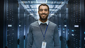 Portrait of a Curios, Positive and Smiling IT Engineer Standing in the Middle of a Large Data Center Server Room.