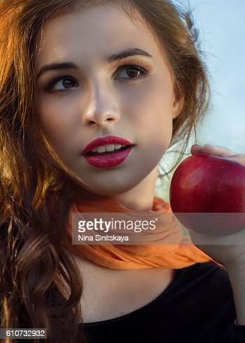 A portrait of a cute woman with red lips holding an apple