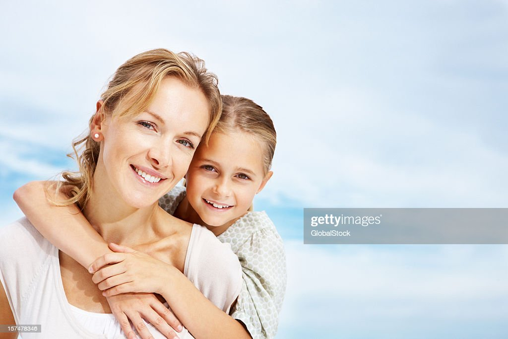 Portrait of a daughter embracing her mother from behind : Stock Photo