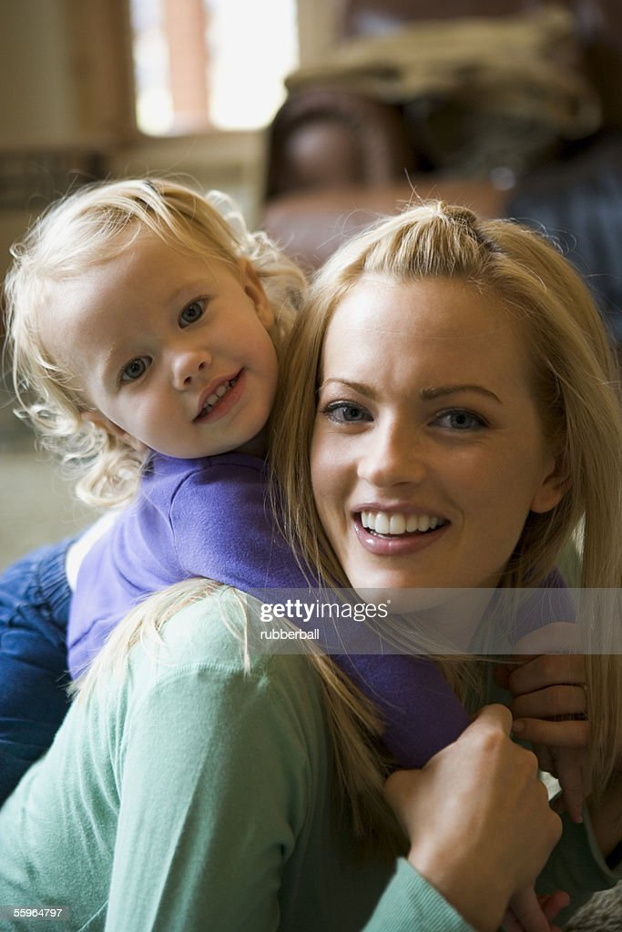 Portrait of a daughter riding piggyback on her mother : Stock Photo