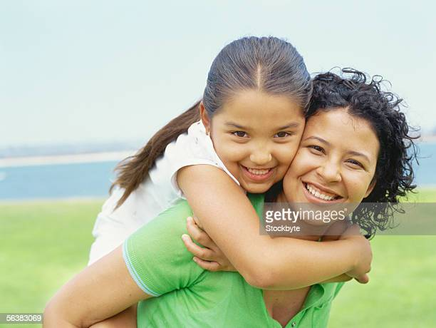 portrait of a daughter riding piggyback on her mother