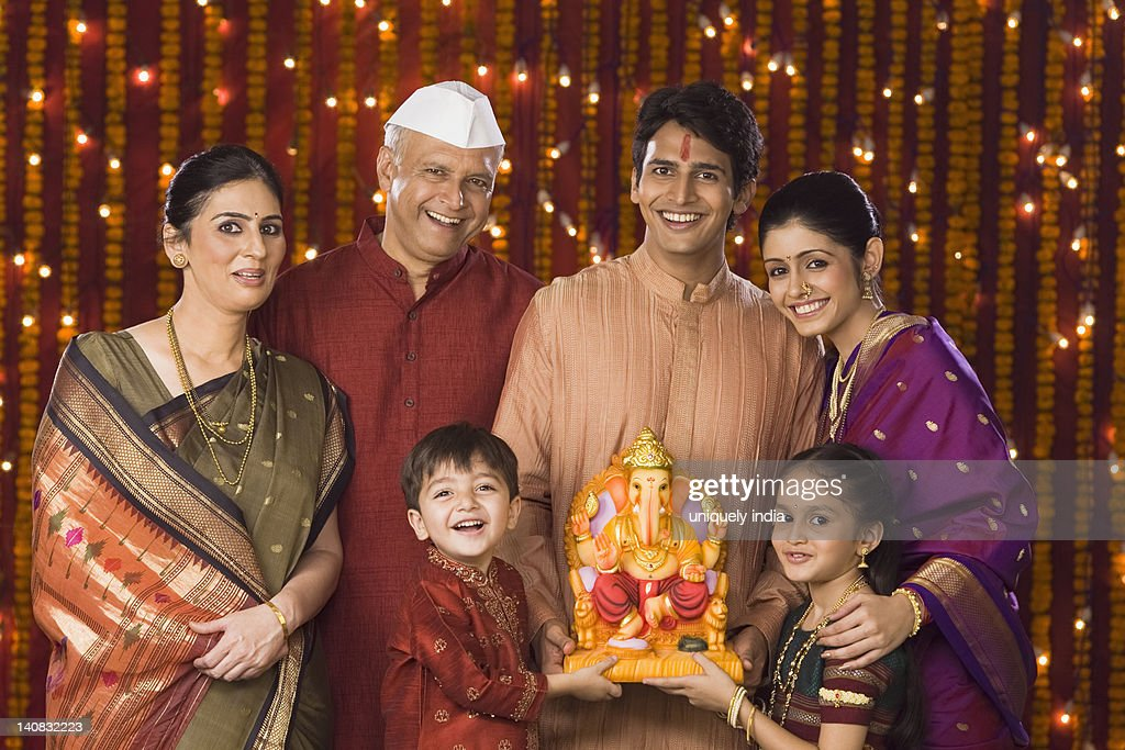 Portrait of a family holding an idol of lord Ganesha