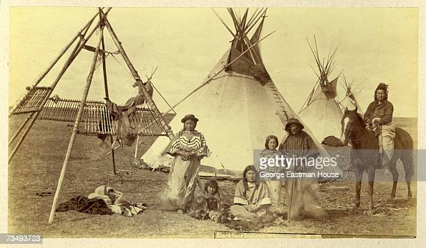 Portrait of a family labelled as 'Blackfeet Indians' as they pose in front of a line of tipis Canada late 1880s Text at the center bottom of the...