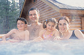Portrait of a Family of Four Relaxing in a Hot Tub in Front of a Snow Covered Chalet