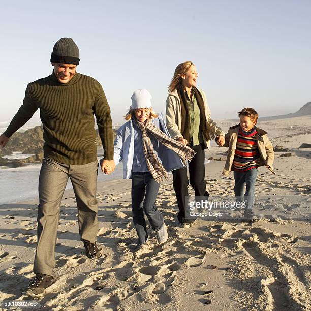 portrait of a family running at the beach