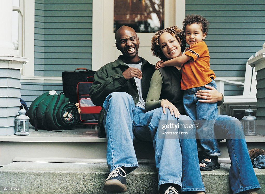 Portrait of a Family Sitting on the Stoop of Their House