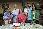 Portrait of a family standing in front of cake at a birthday party