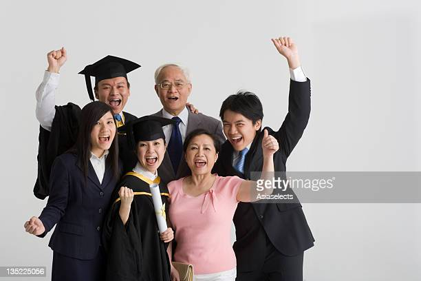 Portrait of a family standing together and laughing with their hands raised