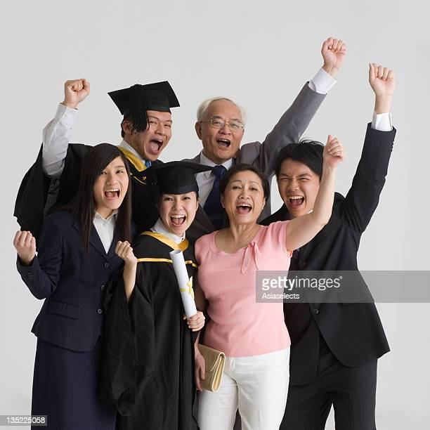 Portrait of a family standing together and shouting with their hands raised