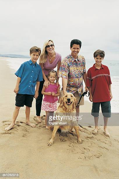 Portrait of a Family With Their Pet Dog on a Beach
