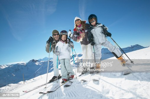 Portrait of a Family With Two Young Children in Skiwear Standing on a Ski Slope