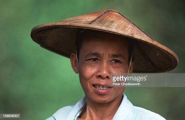 Portrait of a farmer wearing a traditional conical hat in a small rural community