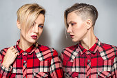 Portrait of a fashion blonde with short hair wearing checkered shirt. studio shot