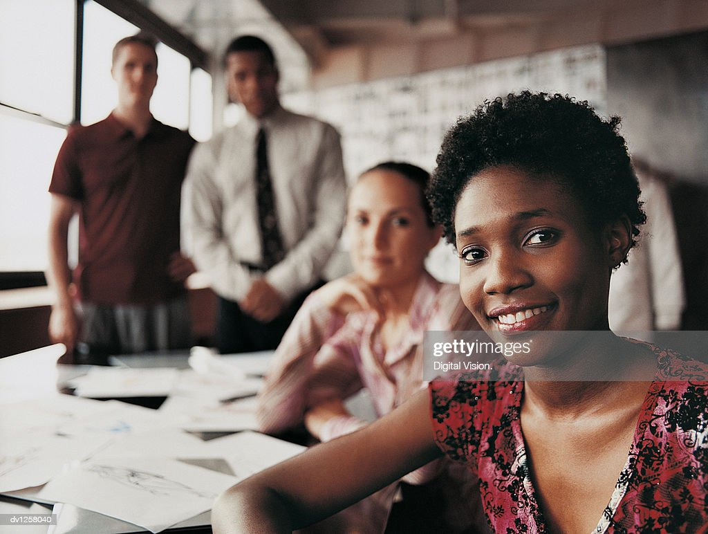 Portrait of a Fashion Designer Sitting in Front of Three of Her Colleagues at a Desk