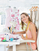 Side view portrait of a young female fashion designer working on her designs in the studio