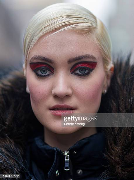 Portrait of a fashion model Victoria Cain with black red eye make up and a wet look blonde hair inspiration seen outside Chiara Boni La petite Rose...