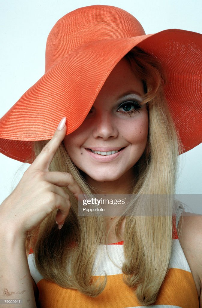 1965, A portrait of a fashionable young woman wearing a large rimmed red straw hat whilst smiling at the camera