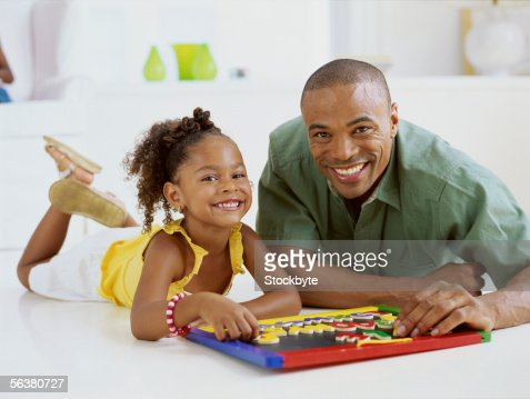 portrait of a father and his daughter playing a board game : Stock Photo