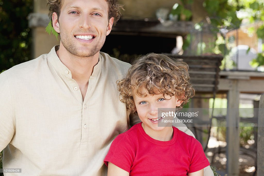 Portrait of a father and son smiling : Stock Photo