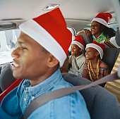 portrait of a father driving with his children (8-10) in a car wearing Christmas caps