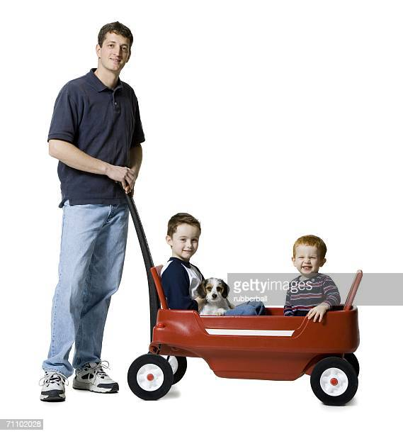 Portrait of a father standing with his two sons sitting in a wagon