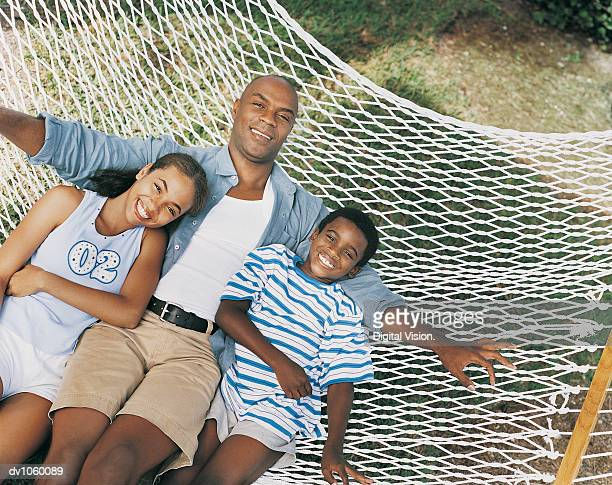 Portrait of a Father with Son and Daughter Lying on a Hammock