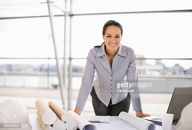 Portrait of a female architect with blueprints smiling at office