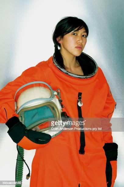 Portrait of a female astronaut holding a space helmet