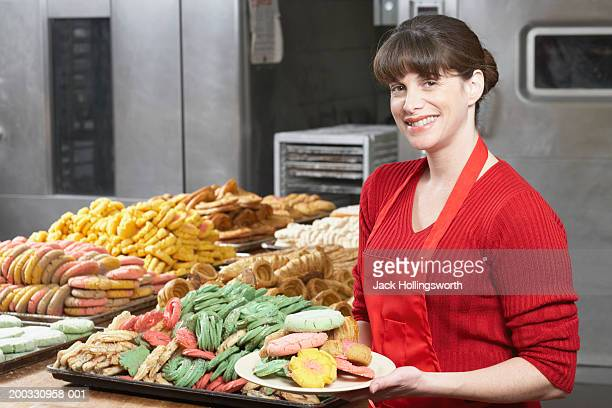 Portrait of a female baker holding a plate of cookies and smiling