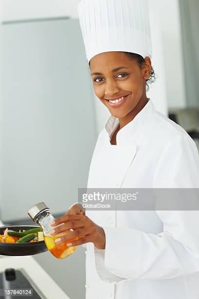 Portrait of a female chef preparing food in kitchen