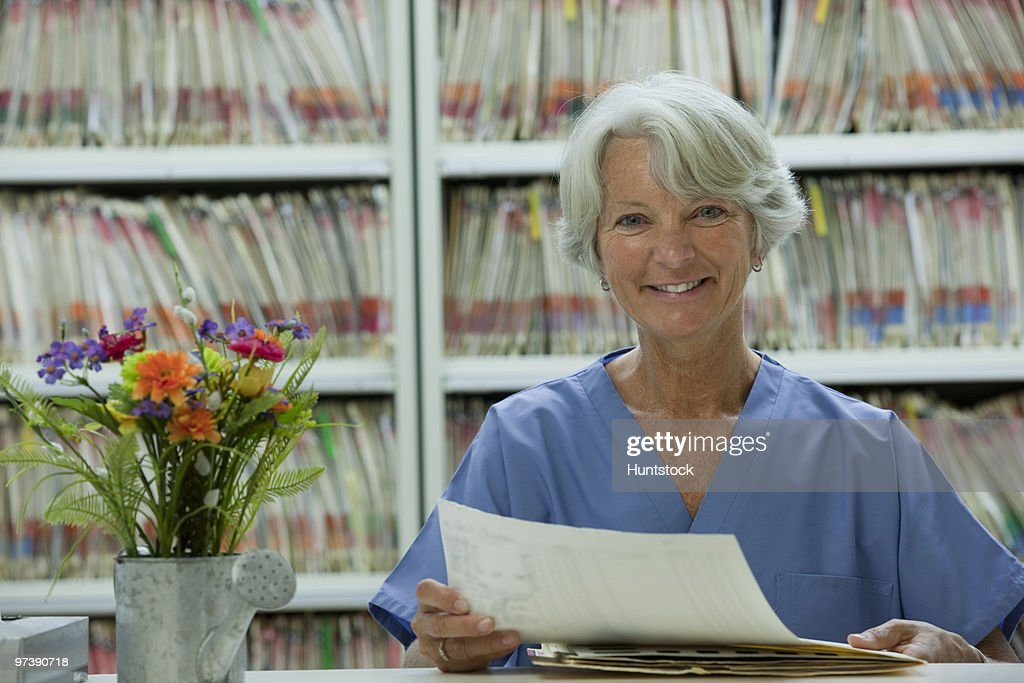 Portrait of a female dental hygienist checking patient records and smiling