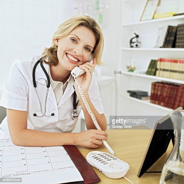portrait of a female doctor talking on the phone at her desk