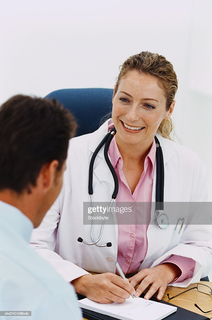 Portrait of a female doctor writing a prescription for a man : Stock Photo