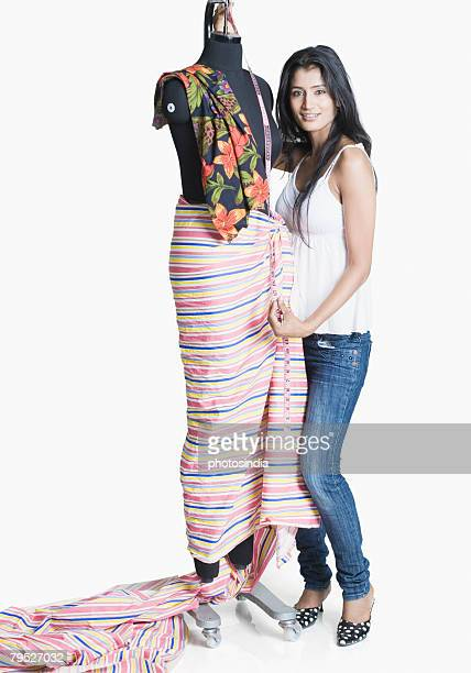 Portrait of a female fashion designer measuring the length of a mannequin with a tape measure