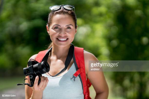 Portrait of a female hiker taking pictures and looking very happy