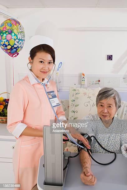 Portrait of a female nurse checking a female patient's blood pressure