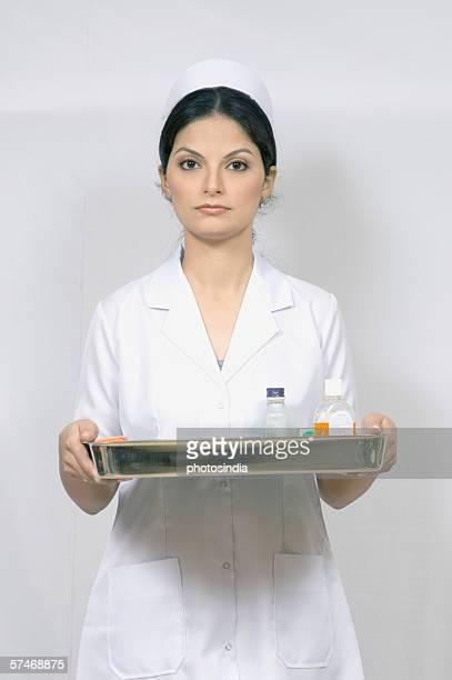 Portrait of a female nurse holding a tray