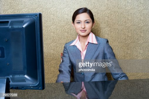 Portrait Of A Female Receptionist Sitting At A Hotel ...