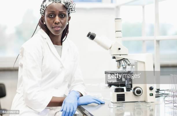 Portrait of a Female Scientist Besides a Microscope