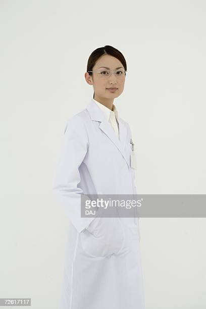Portrait of a female scientist, hands in pocket, looking at camera, front view, white background