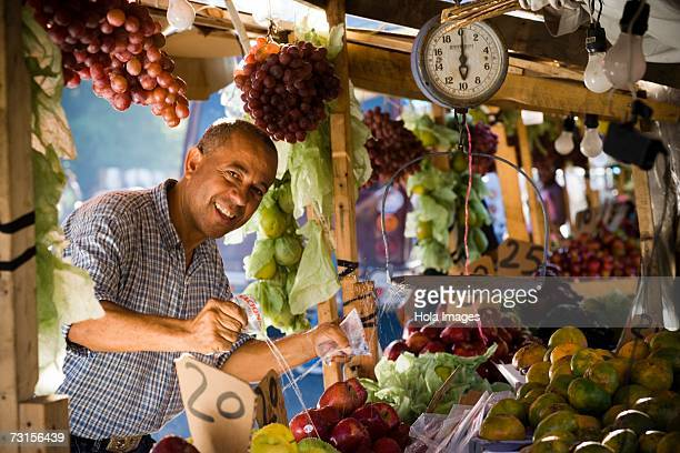 Portrait of a fruit seller splashing water over fruits at a market stall, Santo Domingo, Dominican Republic